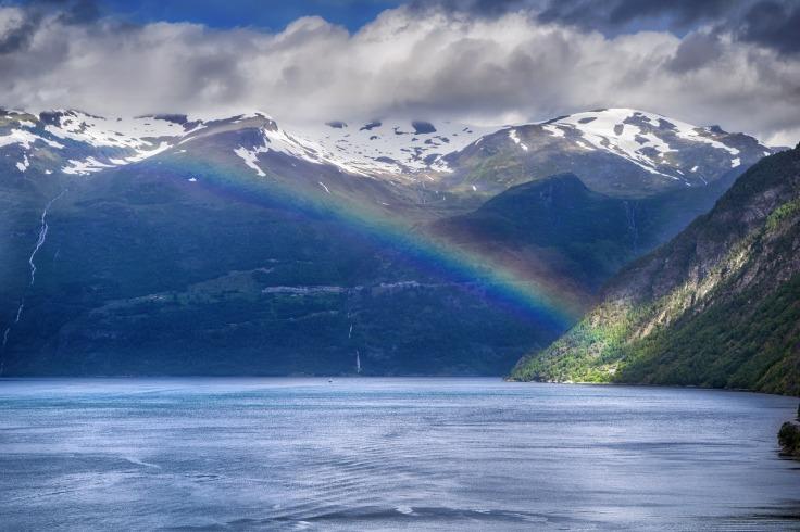 Arc-en-ciel au-dessus d'un fjord et d'une montagne en Norvège