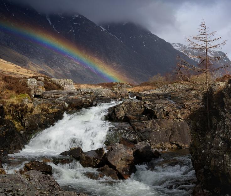 Arc-en-ciel au-dessus d'une rivière et d'une montagne dans les Highlands en Écosse