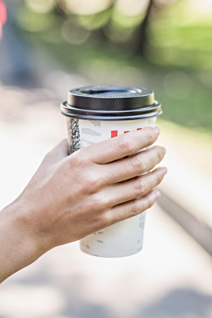 Café pour emporter tenu dans une main