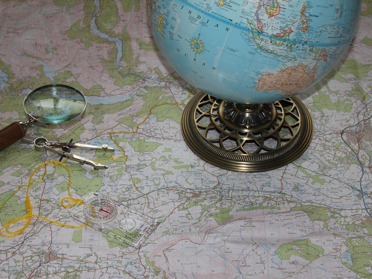 Globe terrestre, loupe et compas sur une carte du monde