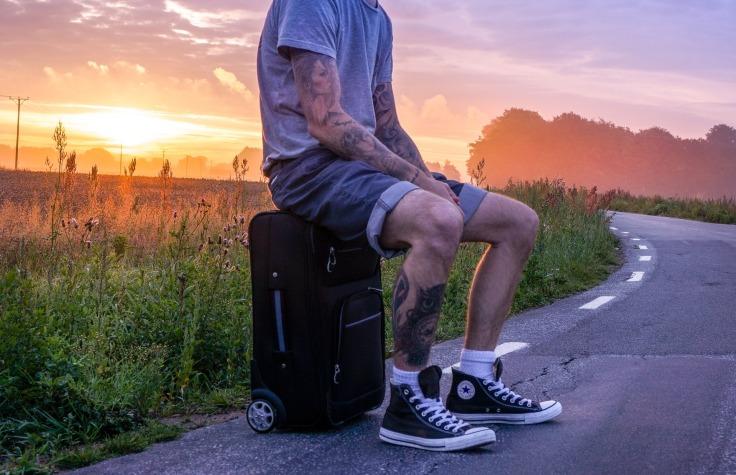 Voyageur tatouage assis sur une valise sur une route déserte