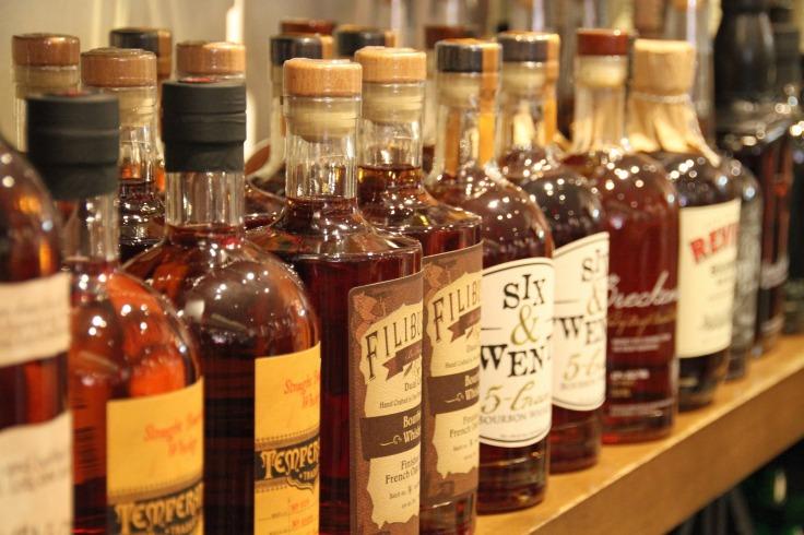 Des dizaines de bouteilles de whisky alignées sur une tablette