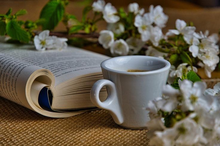 Livre ouvert sur une toile de jute, une tasse blanche et des fleurs blanches