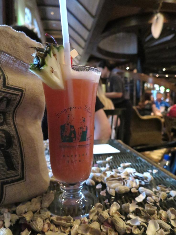 Cocktail Singapore Sling sur une table avec des cacahuètes