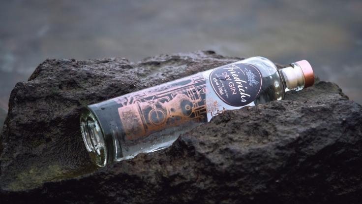 Bouteille de gin sur une roche noire