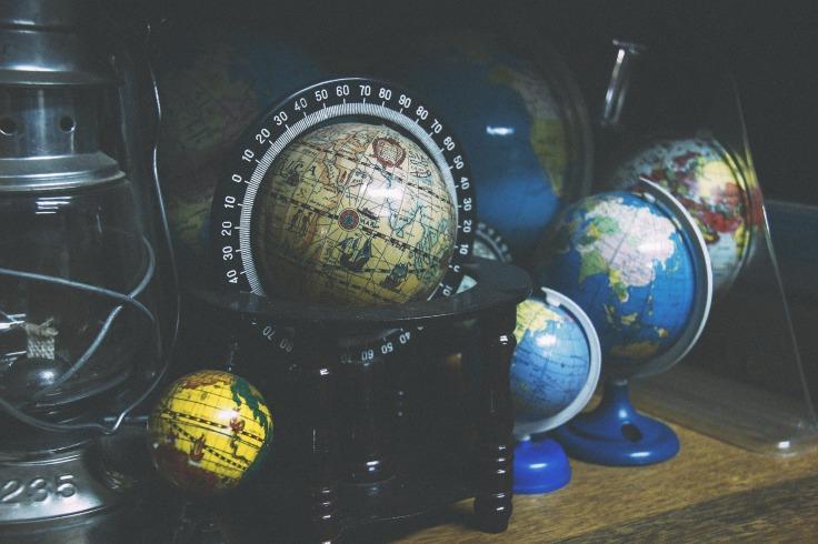 5 globes terrestres bleu, jaune et vintage posés aur un table à côté d'une lanterne