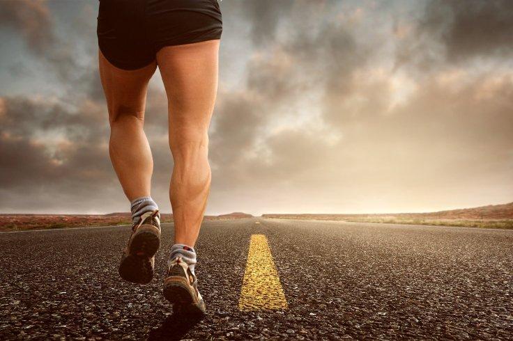 Bas du corps d'un jogger sur une route asphaltée