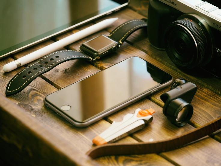 Crayon blanc, iPhone, montre, caméra et lentille sur une table en bois