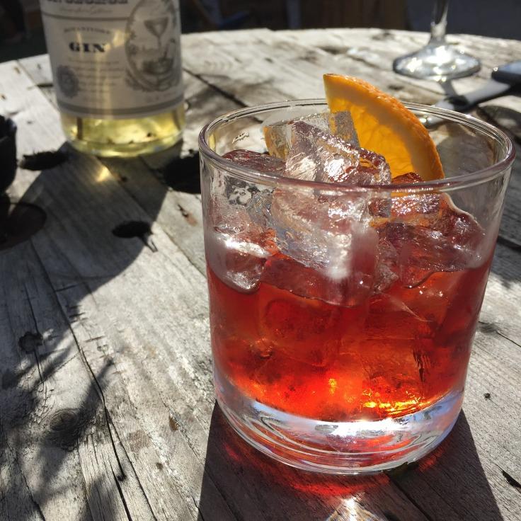 Cocktail Negroni et bouteille de gin sur une table