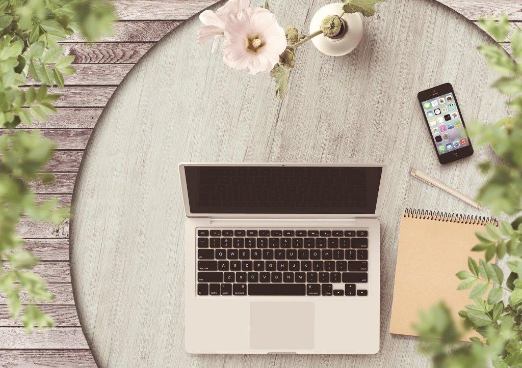 Ordinateur portable sur une table grise, un calepin, un crayon, un iPhone et une fleur rose