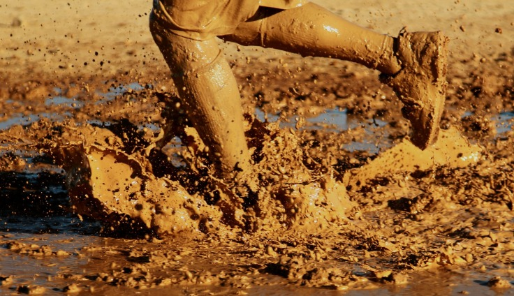 Jambes d'une personne qui court dans la boue