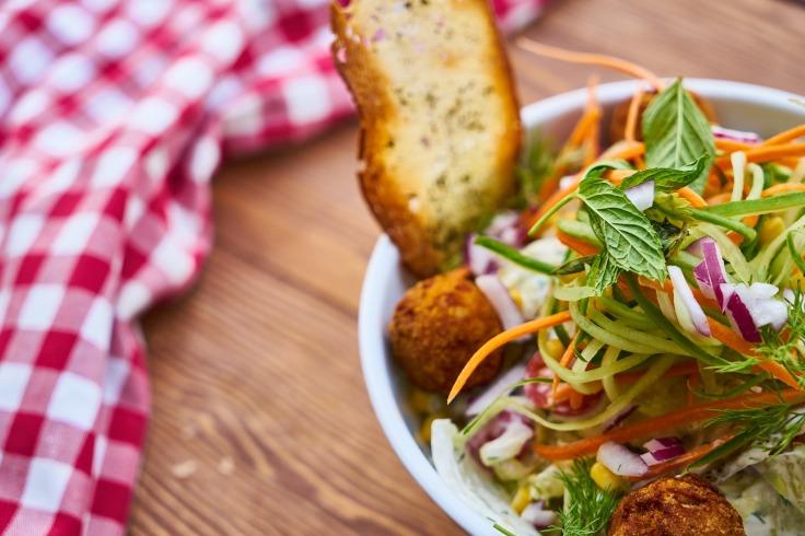 Bol de salade coloré avec légumes et oignon accompagné de pain sur une table en bois et une nappe rouge et blanche