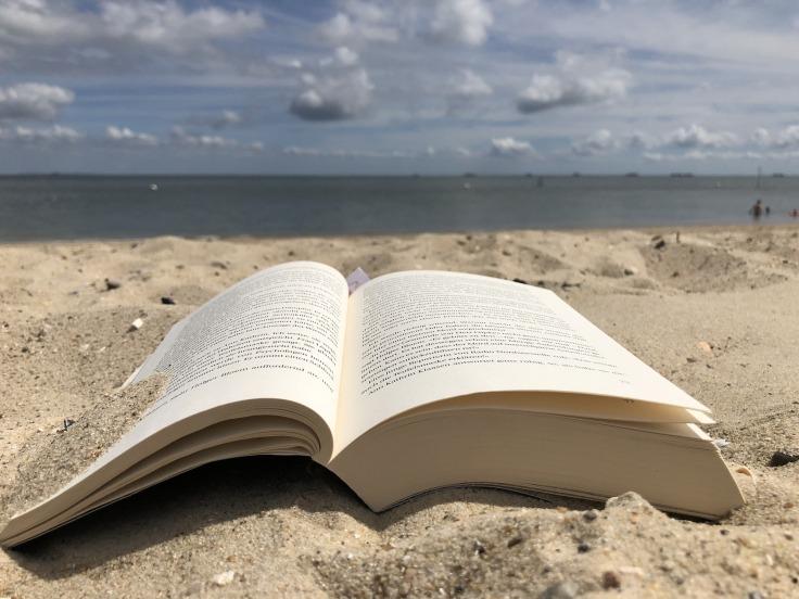 Livre ouvert sur ne plage de sable doré face à la mer