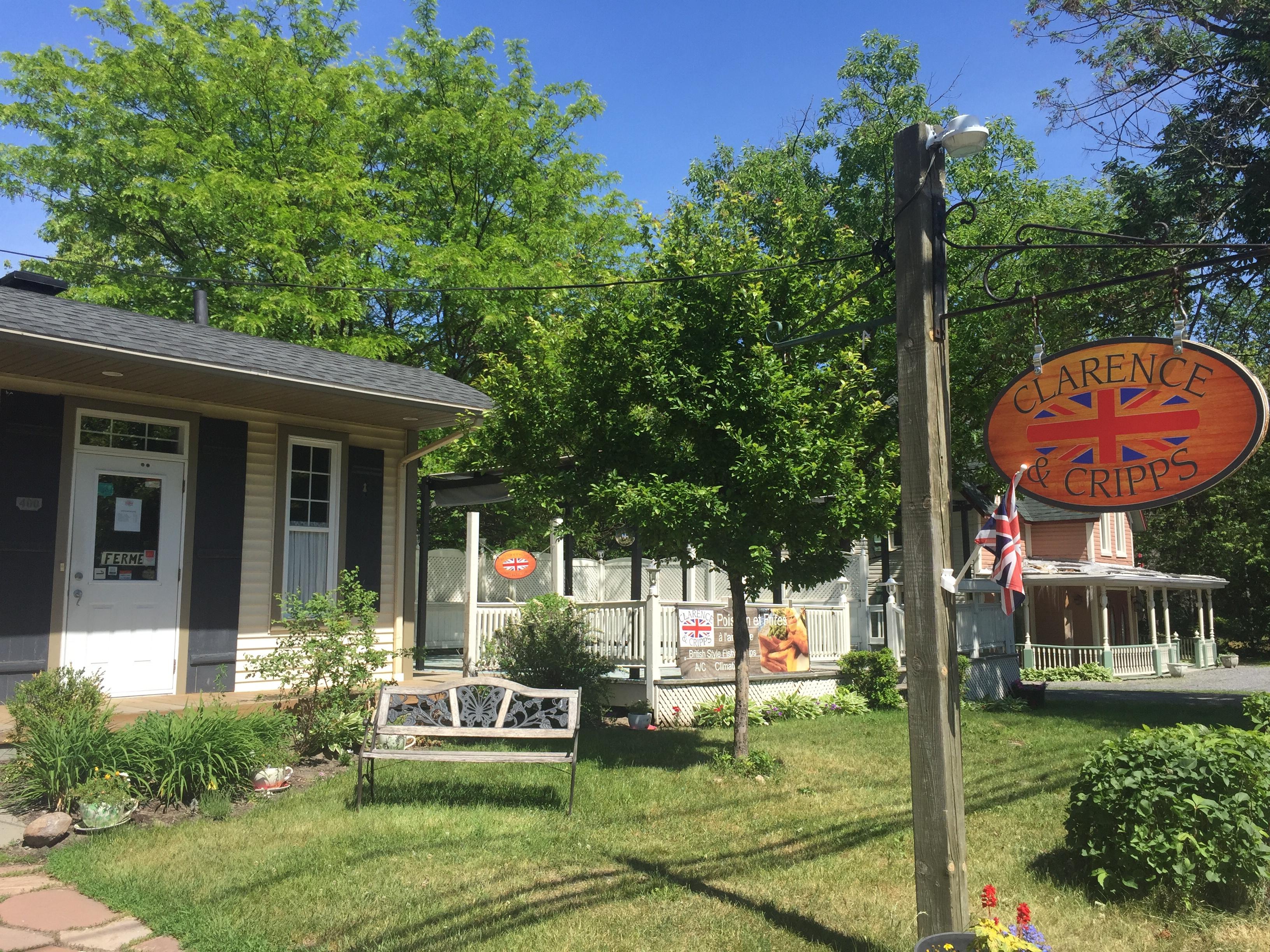 Petite maison, banc de parc, devanture gazonnée et signe en bois sur un poteau