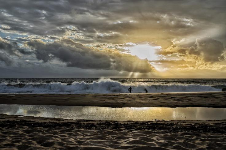 Deux personnes jouant dans les vagues de l'océan au coucher de soleil