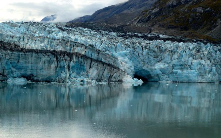 glacier bleu et noir au bord de la mer avec des montagnes