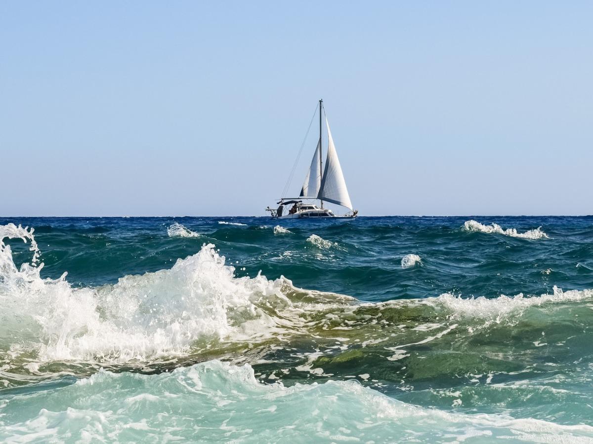Voilier sur une mer bleue agitée, hautes vagues et mousse