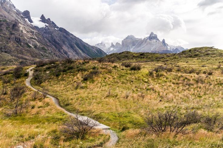 Chemin sinueux à travers une montagne au sommet enneigé et de l'herbe verte