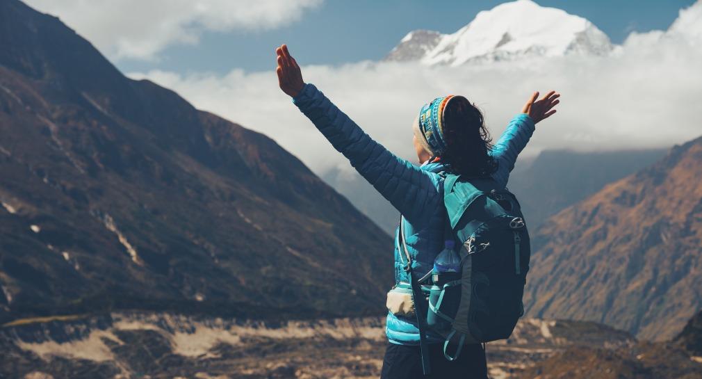 Femme avec sac à dos levant les bras au ciel devant les montagnes, au sommet