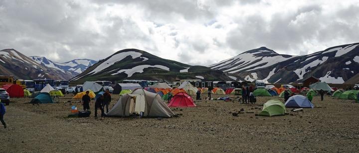 Tentes rouges et bleues et vertes entourés de montagnes et de neige en Islande
