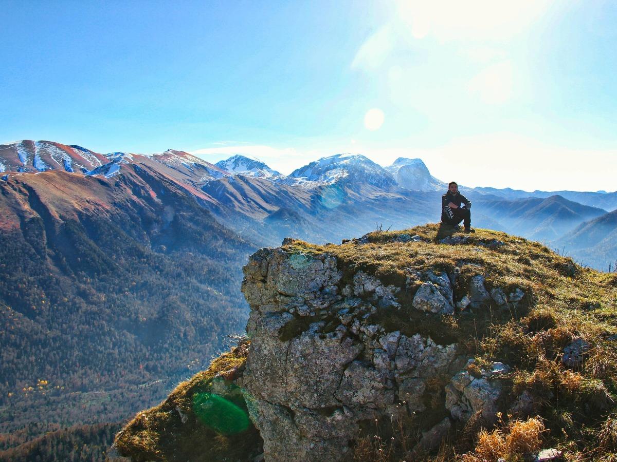 Garçon assis au sommet d'une montagne