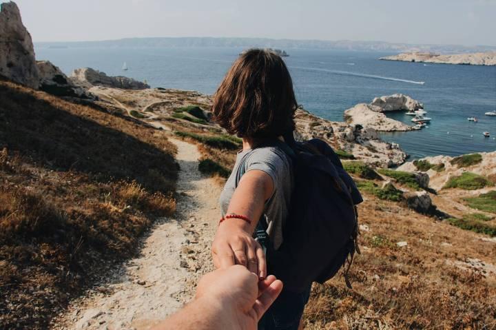 Femme tenant la main d'un homme sur un sentier de roches face à la mer bleue