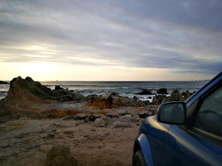 Devant d'une voiture bleue sur une plage de roches face à la mer