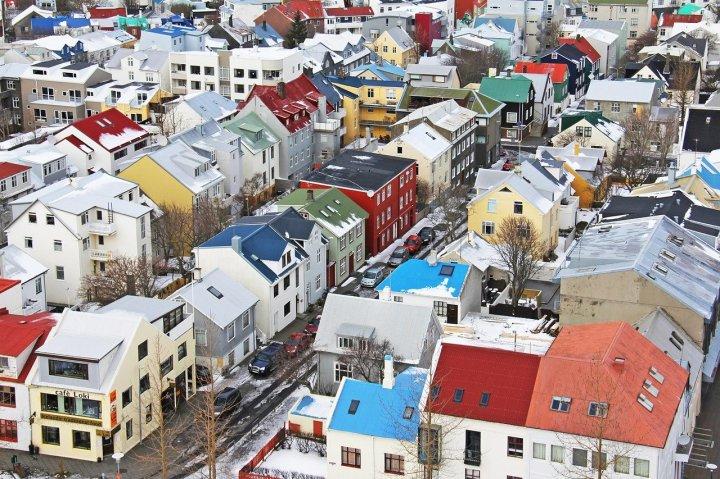 Maisons en rangée aux toits colorés bleus, verts, rouges et jaunes sous la neige.