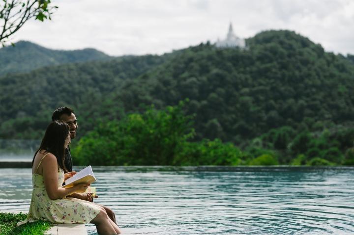 Couple riant et lisant un livre sur le bord de l'eau entouré de montagnes et d'arbres en feuilles