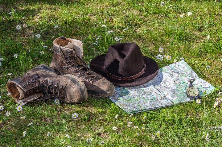 Bottes de randonnée, chapeau, carte et boussole sur du gazon