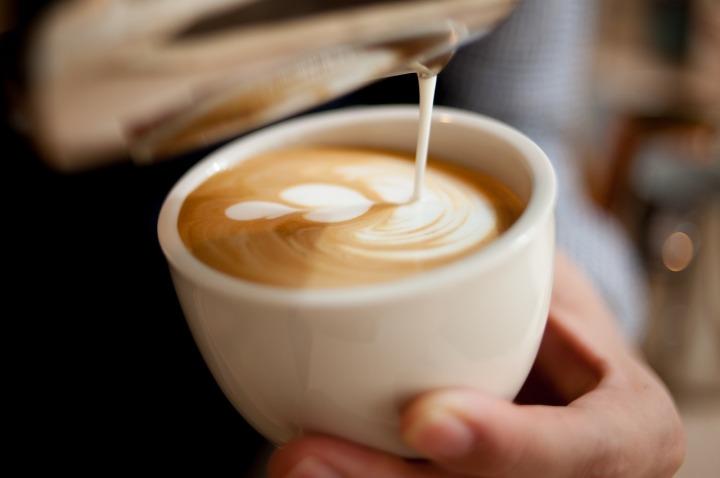 lait moussé et espresso coulant dans une tasse blanche