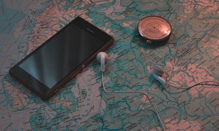 Téléphone Sony, écouteurs, boussole sur une carte géographique/map