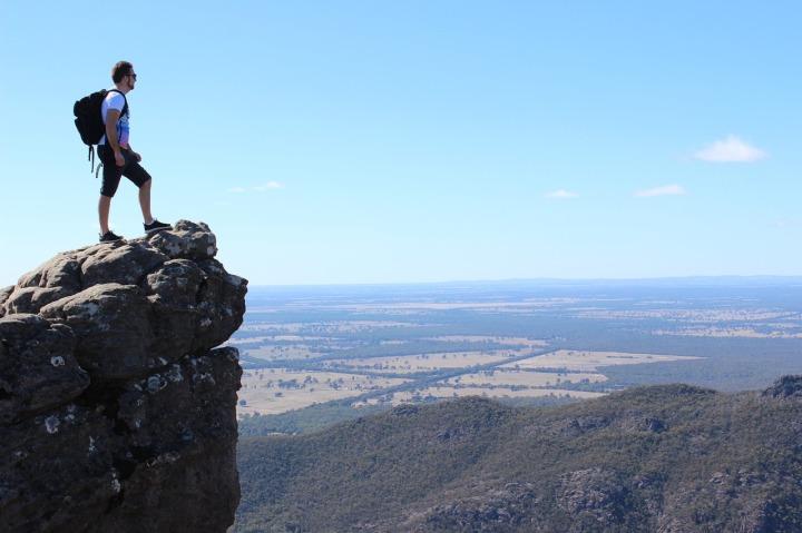 Homme sac au dos au sommet du montagne sur le bord d'un ravin