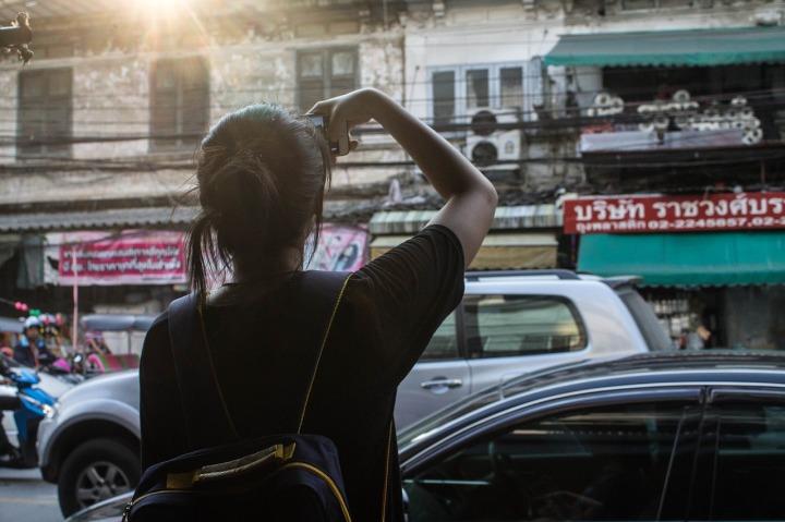 Fille sac au dos prenant une photo d'édifices en voyage