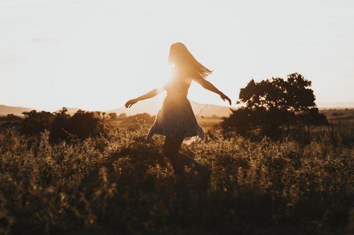 fille-en-robe-dansant-dans-un-champ-d'herbes-hautes