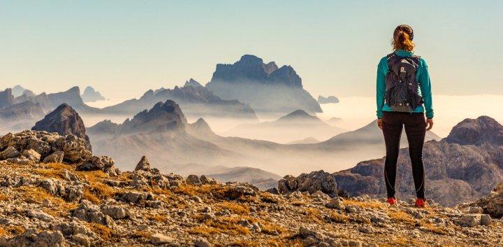 fille sac au dos face à une montagne sur le gazon et la roche