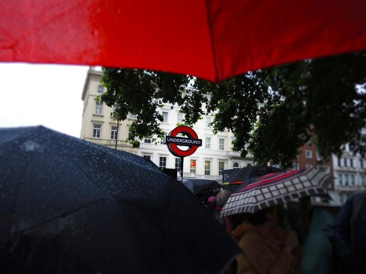 trois-parapluies-ouverts-près-de-l'entrée-d'une-station-du-tube
