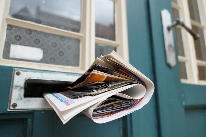 journal-dans-la-fente-pour-les-lettres-et-porte-tuquoise