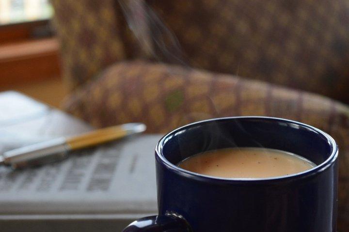 mug-de-thé-bleu-avec-un-crayon-et-un-journal