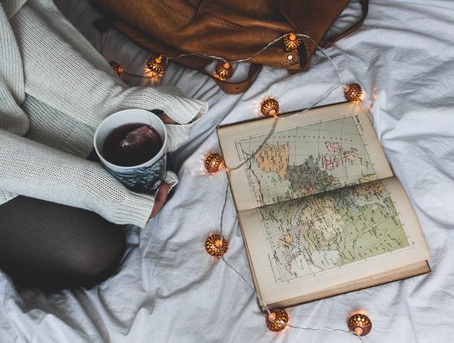 livre-ouvert-carte-géographique-tasse-et-sac-sur-un-lit