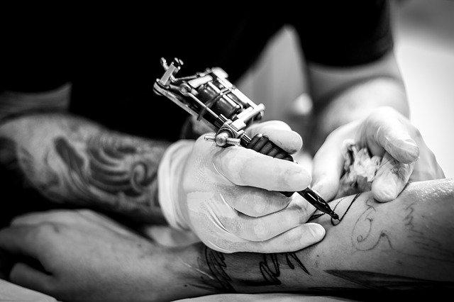 tatoueur-avec-aiguille-dessinant-sur-un-bras