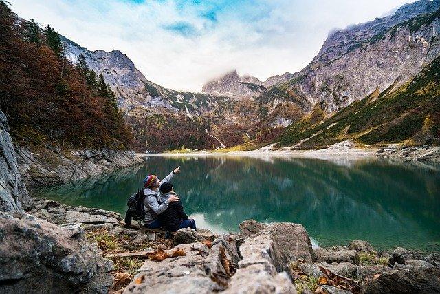 couple-sur-le-bord-dun-lac-et-de-montagnes