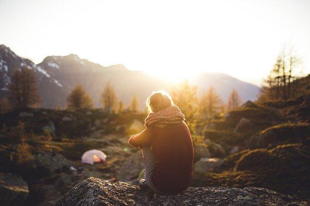 fille-assise-devant-un-lever-du-jour-en-camping