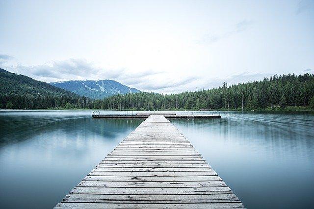 quai-sur-un-lac-bordé-de-sapins-et-de-montagnes